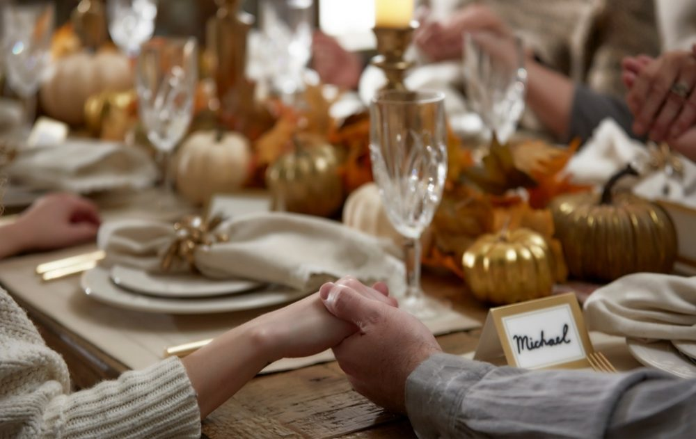 couple holding hands at holiday thanksgiving table