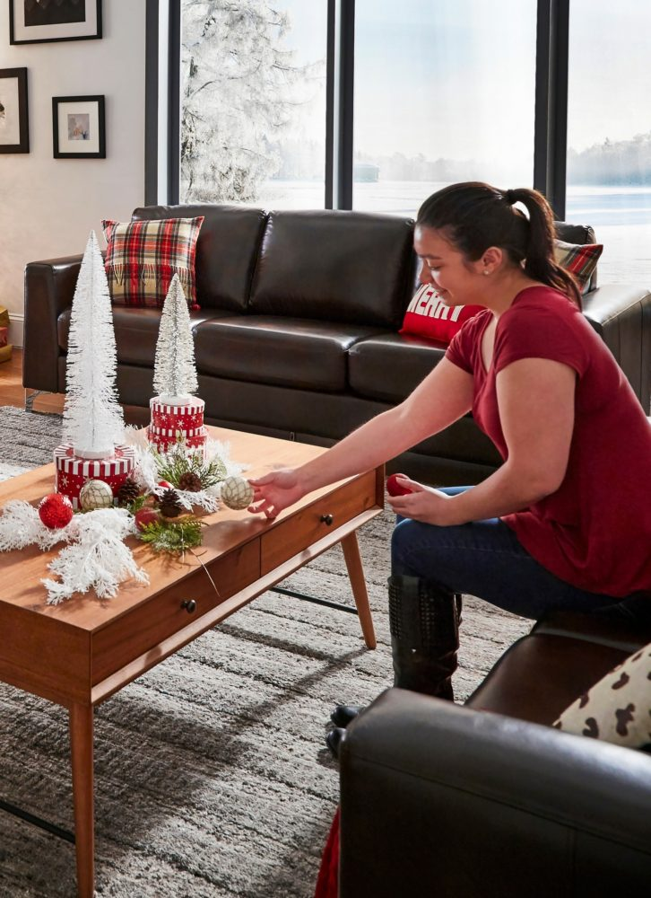 woman decorating coffee table with christmas decor