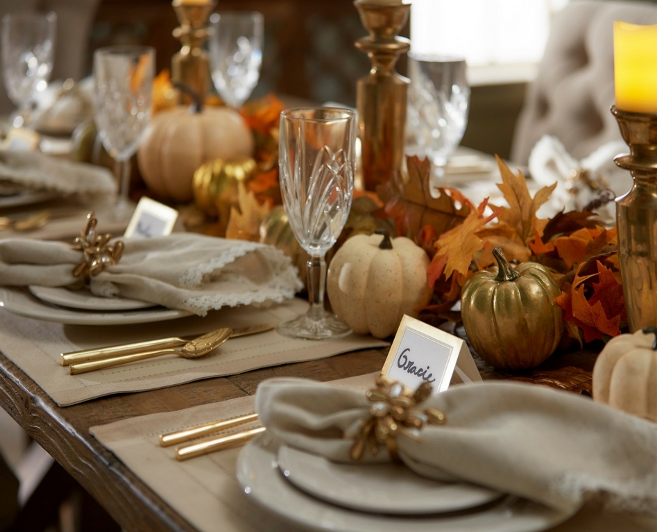 closeup of thanksgiving holiday table with namecards, pumpkins and napkin holders