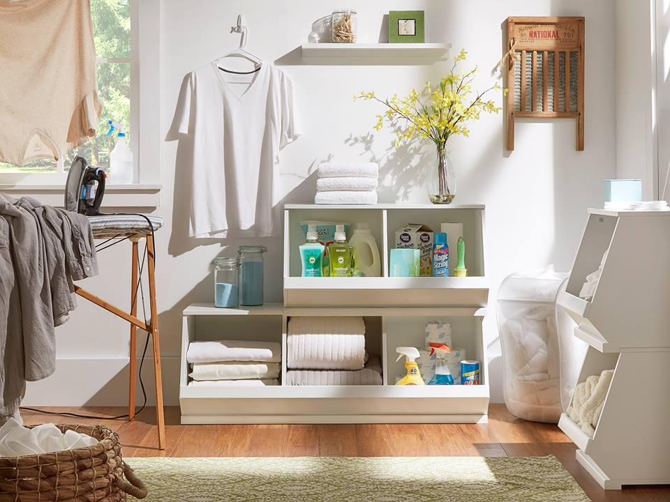 This image is very similar to the one before it. We have 5 white Modular Stacking Storage Bins, with a set of 3 and a set of 2 stacked on top of it. The bins are filled with folded sheets, towels, and all kinds of cleaning supplies. Hanging above the bins is a white t-shirt. Off to the side are 2 white bins stacked on top of each other holding some dirty towels that need to be cleaned.