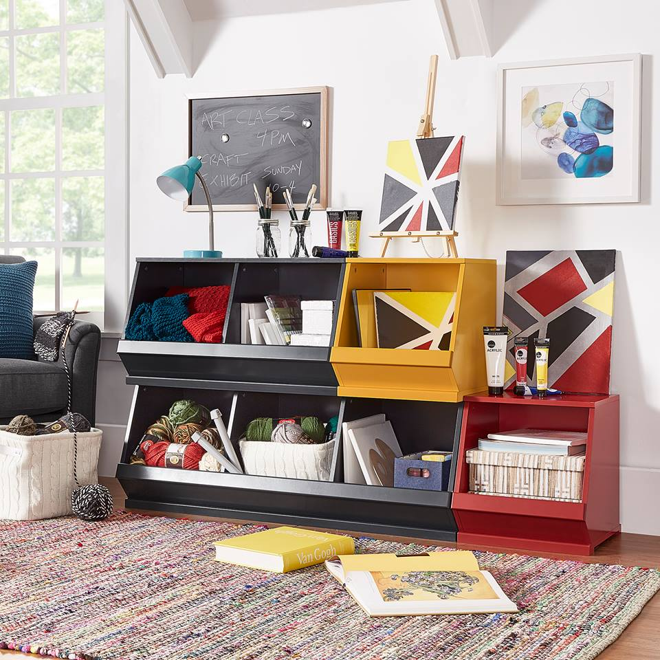 Pictured here are 4 of our Modular Stacking Storage Bins with 3 bins stacked on top. 5 of the 7 bins are in a black finish, while 1 bin is red, and another is banana yellow. All the bins contain craft supplies such as yarn, knitting needles, canvases, paints, and paper. This offers a fun, modern look while keeping art supplies organized.