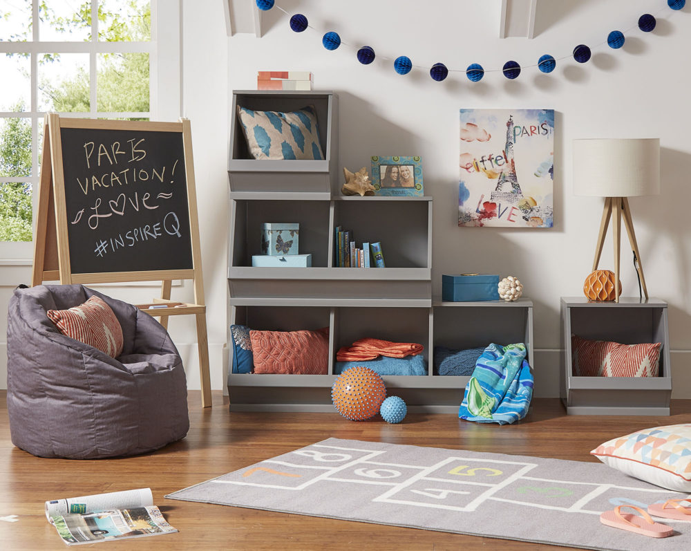 """This is one of the more mature ways to organize your space for kids who might be a bit older. In the center of the room are grey Modular Stacking Storage Bins, with 3 on the bottom, 2 in the middle, and 1 on top in the shape that looks like a staircase. The bins are filled with blankets, pillows,     and books, while the top of the bins are used as extra surface space for photos and a table lamp. Since we were going for a Paris theme, there is a painting of the Eiffel Tower on the wall above the bins, and a chalkboard to the side has """"Paris Vacation!"""" written on it."""