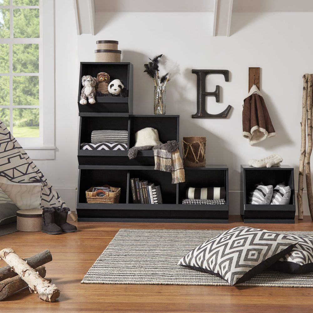 This one of our ways to organize your space is a modern look for an outdoorsy-themed space. We used black Modular Stacking Storage Bins (3 on the bottom, 2 in the middle, 1 on top, and 1 off to the side). The bins feature black and white household items, including blankets, pillows, books, and even some clothing articles. There are also some stuffed animals added to enhance the outdoorsy theme to the overall space.