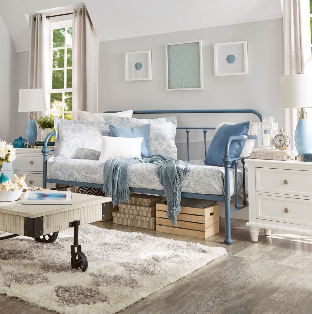 This is another one of our spring style ideas for daybeds with our blue, Victorian-styled metal daybed. This room features the same antique white wood and metal coffee table, as well as a white wood 2-drawer nightstand. The blue daybed has blue and white paisley-print bedding, with a blue throw blanket, blue pillows, white pillows, and matching blue and white paisley print pillows.