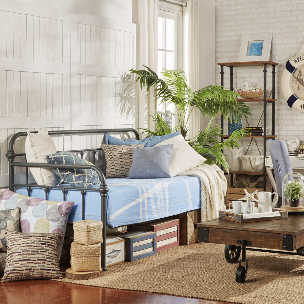 This is the last of our spring style ideas for daybeds. The black Victorian-styled metal daybed has a more coastal theme to it, with light blue bedding, brown, white, and blue pillows, and a brown wood and metal coffee table in front of it.
