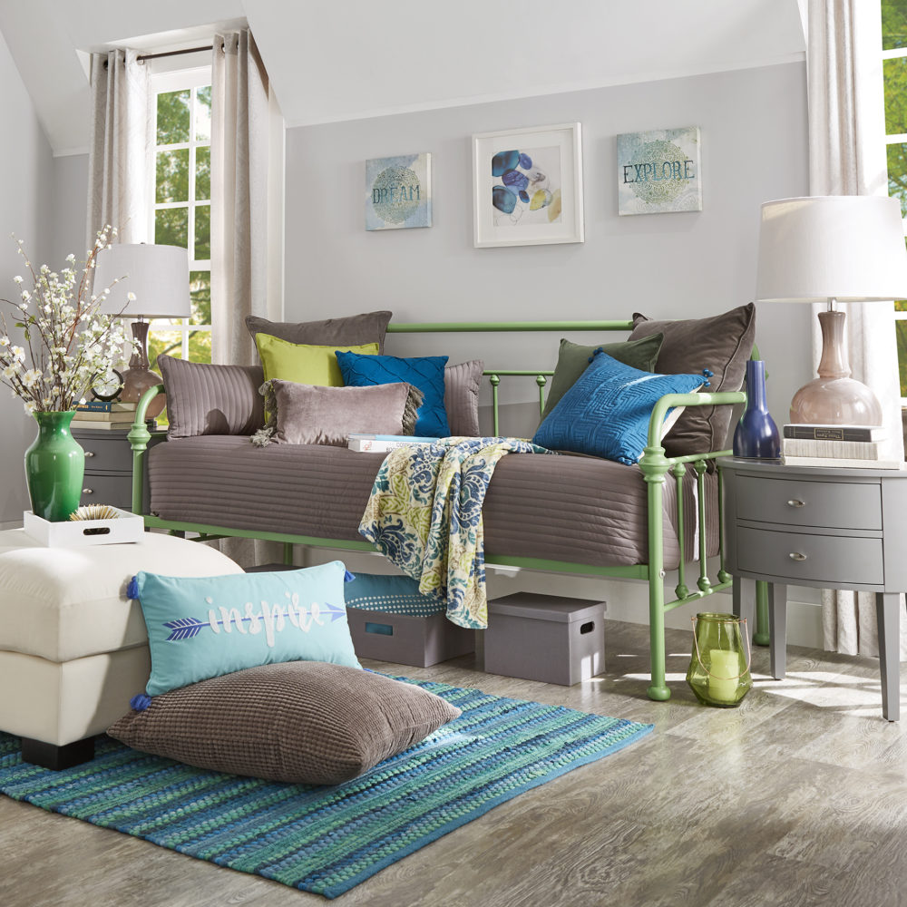 Our green-finished, Victorian-inspired metal daybed is dressed with grey bedding. There are some blue and green pillows to add a pop of color and complement the green finish of the daybed. There is also a white linen ottoman and a grey finish 2-drawer nightstand by the daybed.