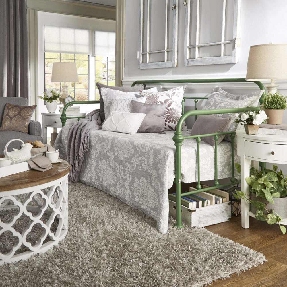 The next of our spring style ideas for daybeds features the same Victorian-inspired metal daybed, but this time it is in a meadow green finish. This look has a more feminine, farmhouse theme with grey and white paisley print bedding, with white and grey pillows with a variety of textures and prints. This image also features a white and oak coffee table and a white 1-drawer end table decorated with greenery.