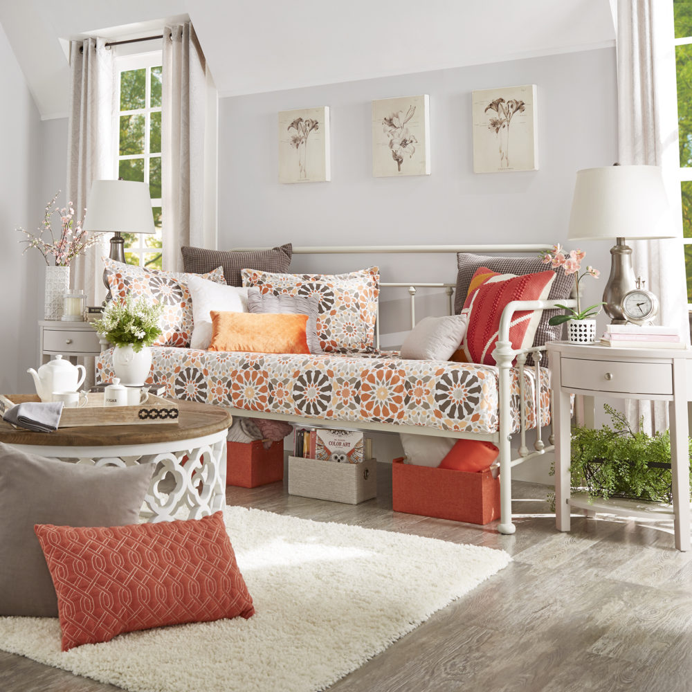 This is another more feminine look of our spring style ideas for daybeds. The white finish Victorian daybed has pink, orange, grey, and white printed bedding. There is also a white and oak coffee table in front of it and a white 1-drawer nightstand to the side.