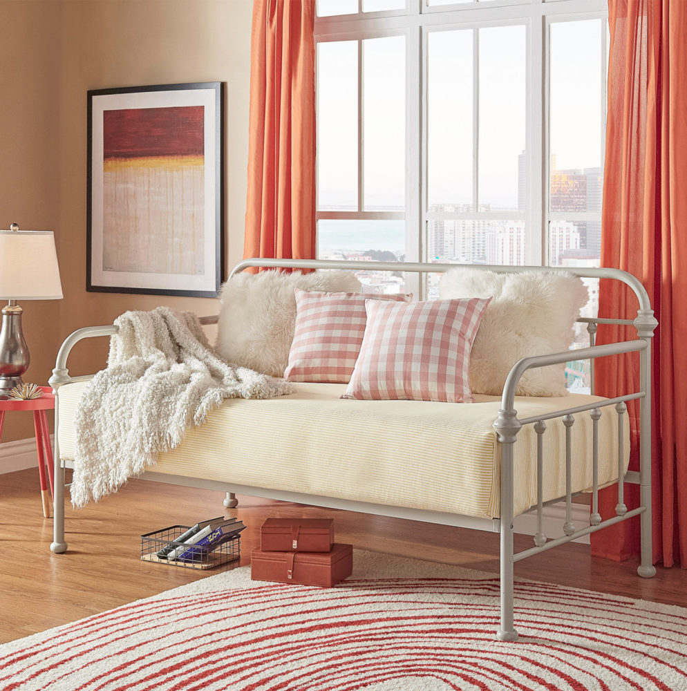 This one of our spring style ideas for daybeds uses the white finish of our Victorian metal daybed. This look is crisp, clean, and slightly feminine, with buttery yellow sheets, fluffy white pillows, and pink and white checkerboard pillows. There are also peach-colored curtains hanging behind the daybed while there is a white and red rug on the hardwood floor.