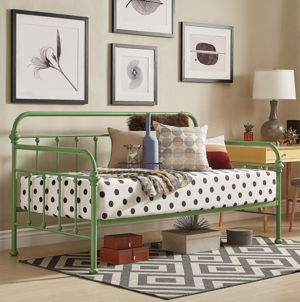 This is a third look featuring the green finish Victorian-styled metal daybed. This look offers a more modern aesthetic, with black and white polka dot sheets with muted-colored pillows. There is also a geometric black and white printed rug with a few decorate boxes placed underneath the daybed.