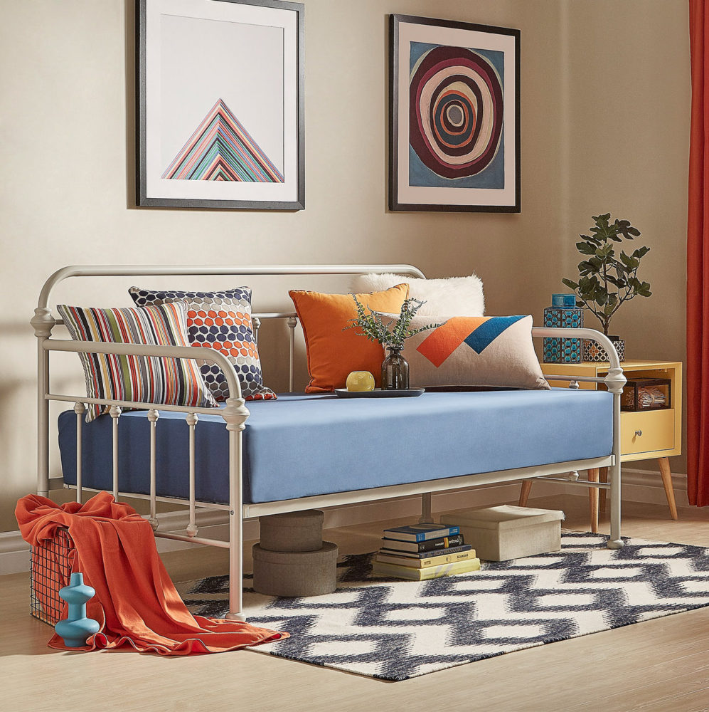 For this one of our spring style ideas for daybeds, our white Victorian metal daybed features a more modern look. The mattress has a crisp blue sheet, while the pillows are blue, white, and orange with various prints. There is also a matching orange throw blanket to the side, and a black and white zigzag printed rug.