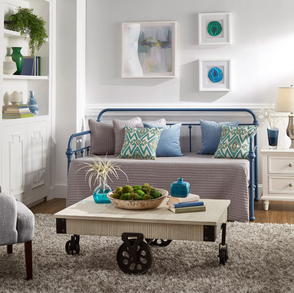 This first image displays a room with a blue-finished Victorian style daybed with grey bedding. There is a grey blanket, grey pillows, blue pillows, and some blue and white printed pillows. In front of the daybed is an antique white wood and metal coffee table. And next to the daybed is a white wood 2-drawer nightstand with a table lamp on top.