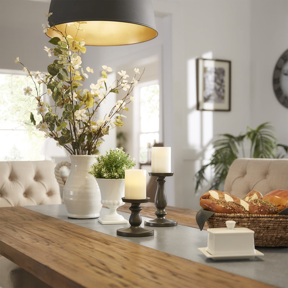 This is a close-up shot for the farmhouse theme. It features the Rustic Pine Concrete Inlaid Table Top Dining Table, decorated with candles, white vases filled with greenery, and a basket of bread.