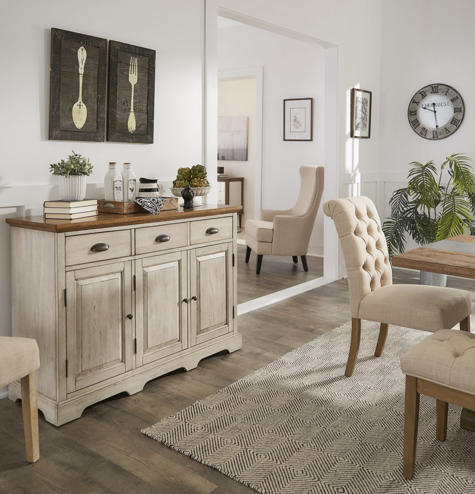 This image shows one of the beige linen button tufted parsons chair and the antique white finish server. Hanging above the server are portraits of a spoon and fork for the farmhouse theme.
