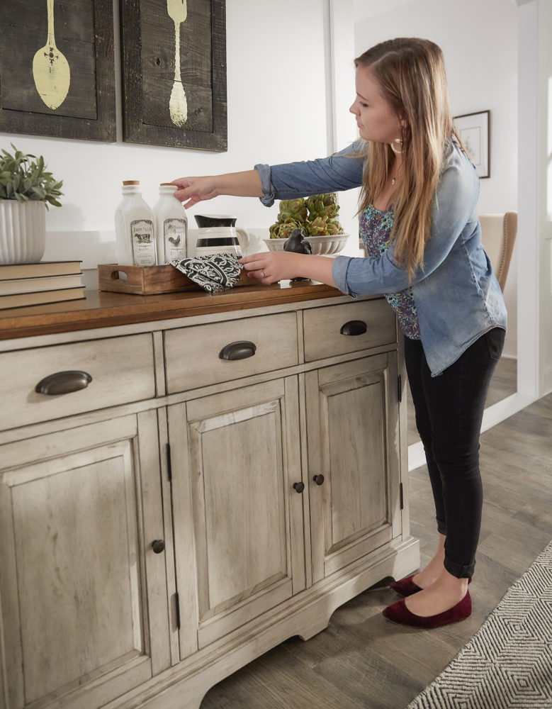 This image features our designer setting a tray down on the antique white finish server. The wood server has an oak table top, which holds a stack of books, some potted plants, and a tray with some old fashioned glass milk bottles.