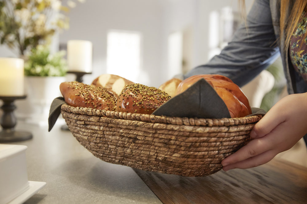 An image of our designer placing a basket of bread on the dining table. This image also highlights the contrast of the grey concrete inlaid against the pine wood table top.