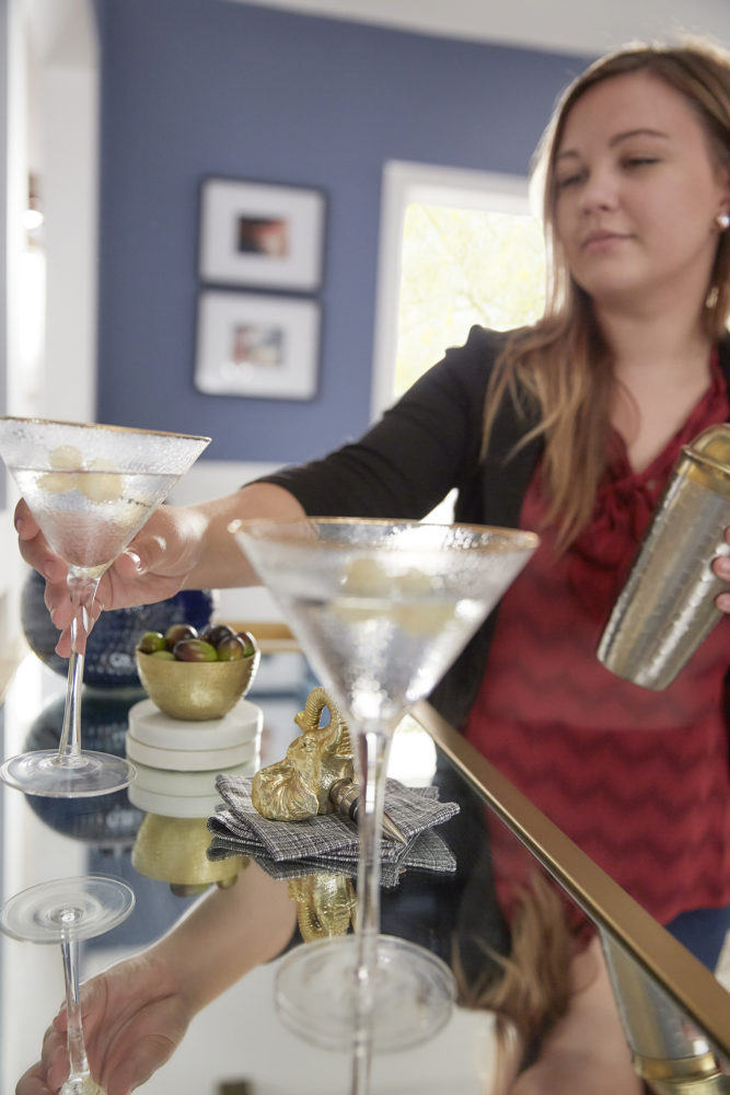 This image features our designer setting martini glasses down on our gold finished metal clear tempered glass bar cart.