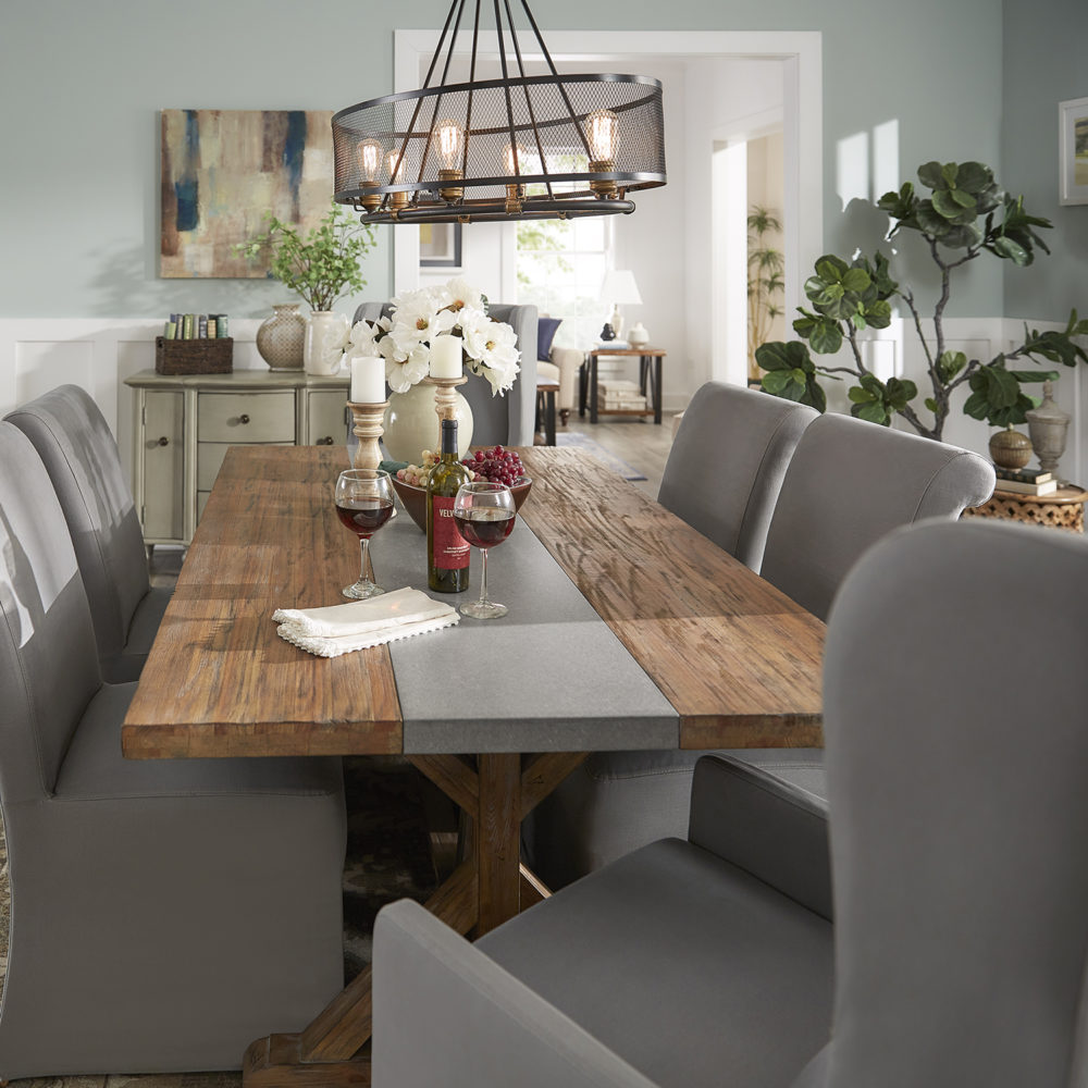 This image is the last of our dining table ideas. This is a classic look that is timeless, inviting, and elegant. It features the same Rustic Pine Concrete Inlaid Table Top Dining Table, four grey cotton slipcovered side chairs, and two grey slipcovered arm chairs. The table top is decorated with a vase of flowers, some candles, a bowl of grapes, and some wine glasses.