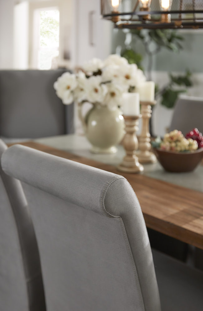 This is a closeup shot of one of the grey cotton slipcovered side chair. The top of the chair is rolled slightly for added sophistication.