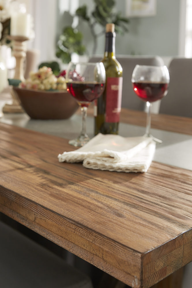 This is a closeup shot of the dining table. It showcases the pine wood grain finish set against the grey concrete inlaid. There are two wine glasses filled with red wine.