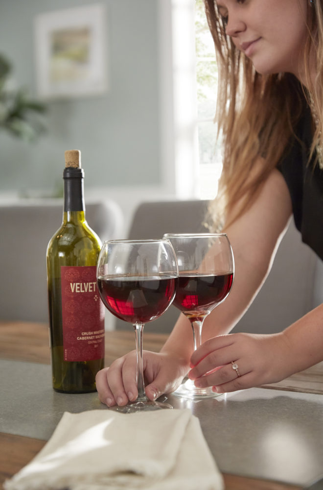 This image shows our designer placing two wine glasses of red wine on the concrete inlaid of the table top.