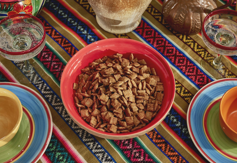 Pictured is a bowl full of Chex mix.