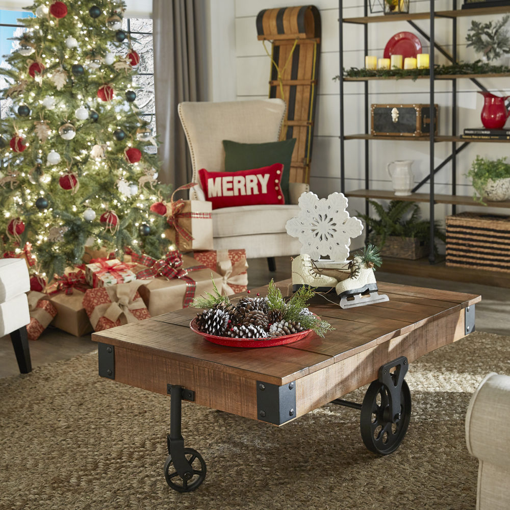 In this image, our wood and metal coffee table is decorated with a red plate of snow-dusted pinecones and decorate snowflakes and ice skates.