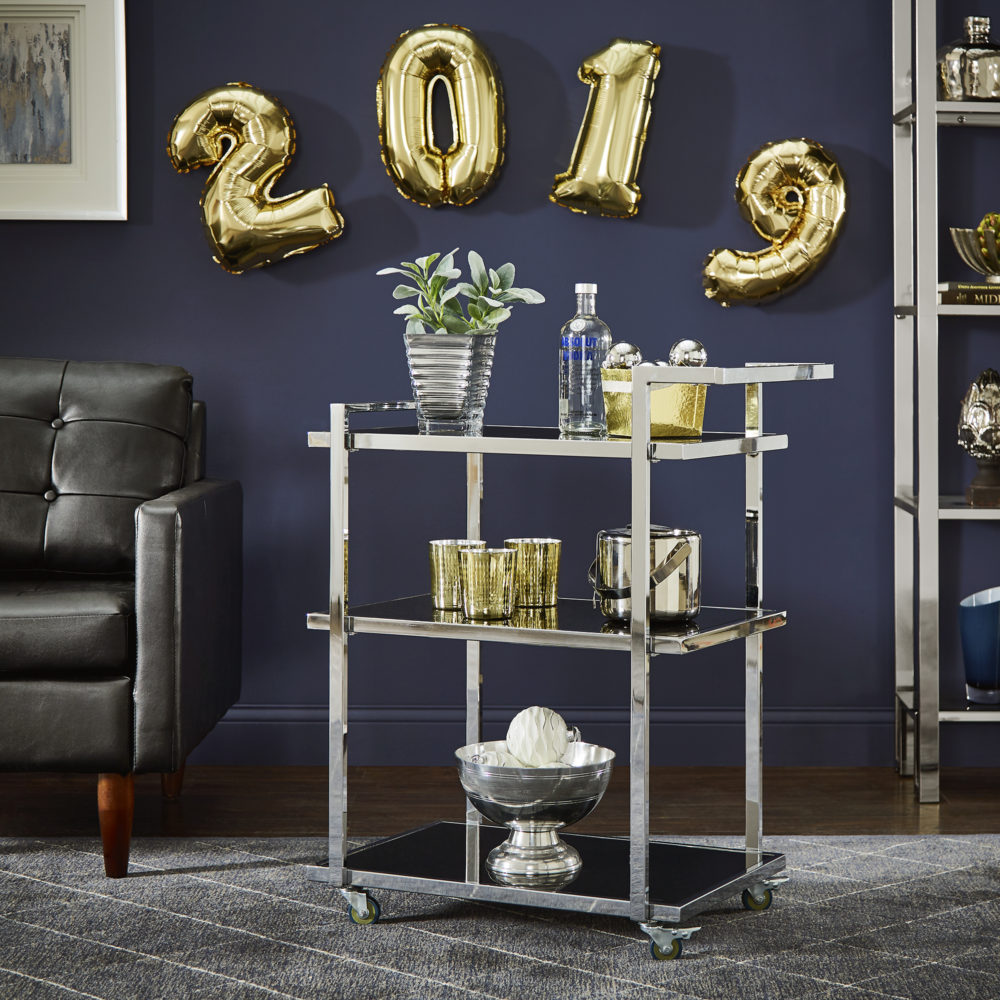 """This image features the full rectangular, chrome bar cart with black tempered glass shelves. The top shelf is decorated with a succulent, a bottle of vodka, and a gold bowl of chrome ornaments. The middle shelf has gold and chrome barware. And the bottom shelf has a chrome bowl with white accessories in it. Hanging on the wall above the bar cart is gold balloons that say """"2019."""""""