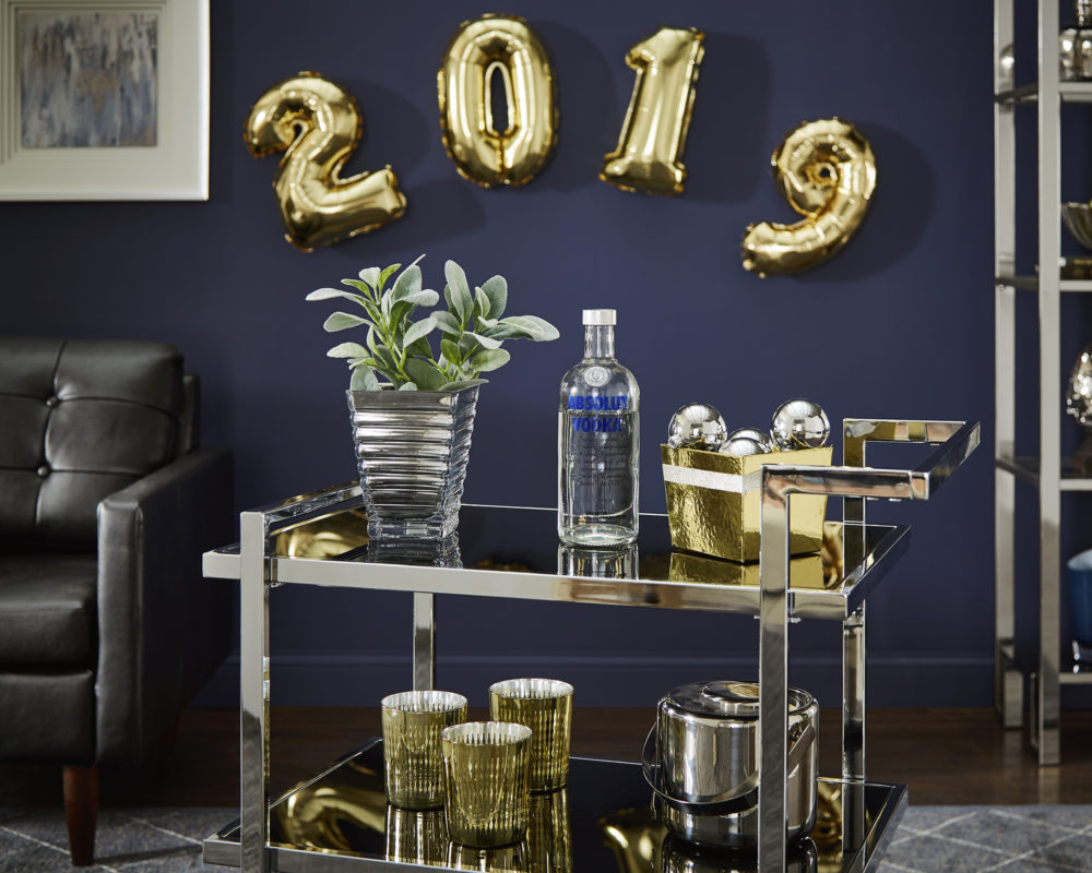 """This image features another view of the top and middle shelves of a rectangular, chrome bar cart with black tempered glass shelves. The shelf is decorated with a succulent, a bottle of vodka, and a gold bowl of chrome ornaments. Hanging on the wall above the bar cart is gold balloons that say """"2019."""""""
