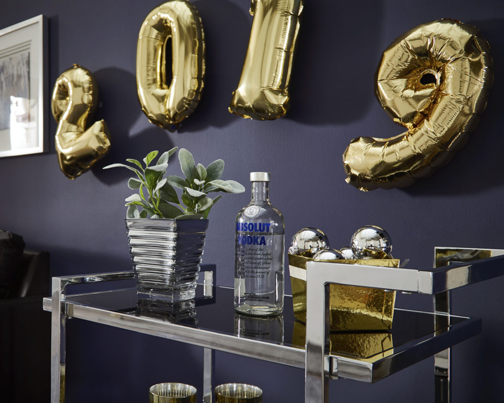 """This image features the last of our New Year's décor ideas. It focuses on the top shelf of a rectangular, chrome bar cart with black tempered glass shelves. The shelf is decorated with a succulent, a bottle of vodka, and a gold bowl of chrome ornaments. Hanging on the wall above the bar cart is gold balloons that say """"2019."""""""