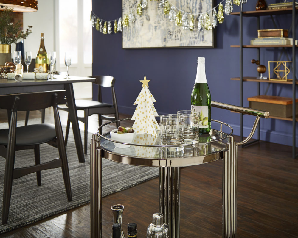 This bar cart puts a classic Hollywood spin on our New Year's décor ideas. This glamorous gold bar cart is decorated with a tiny white pine tree and a bowl of olives, in addition to the bottle of wine and glasses.