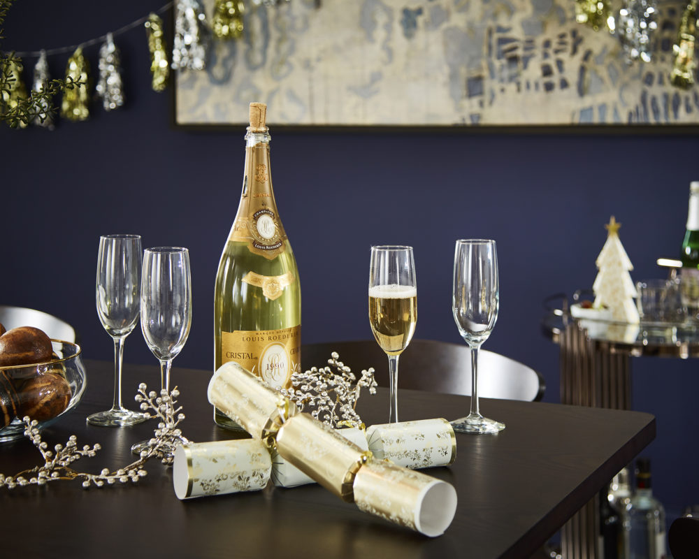 This image is the third of 4 New Year's décor ideas. This image showcases a dining table with a bottle of champagne and four champagne flutes in the foreground. In the background is an out-of-focus bar cart.