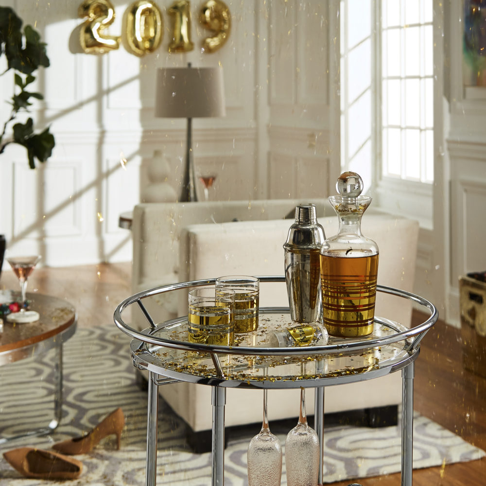 This image is the second of 4 New Year's décor ideas. This is an image of our round chrome finish clear tempered glass metal bar cart. This is the most minimalist of all our New Year's décor ideas, as the only decor comes from gold confetti and the barware itself.