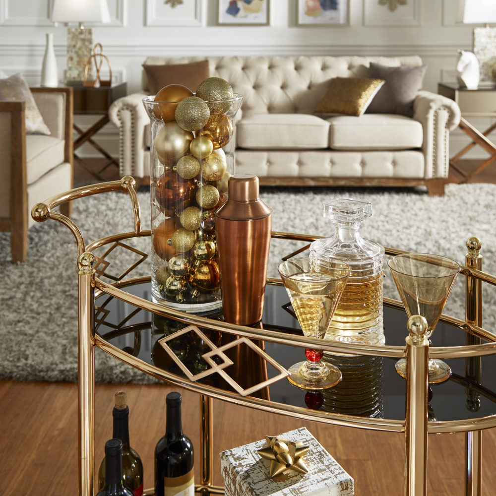 This image is the first of 4 New Year's décor ideas. It displays our Rose Gold Finish Black Tempered Glass Metal Bar Cart. It is decorated with gold accessories, including gold-tinted glassware and a jar full of sparkly gold ornaments for a glamorous look.