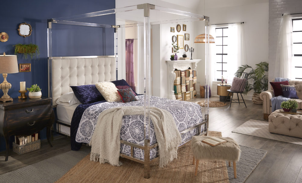 This image shows the full bedroom of our bohemian interior design. In the center is our acrylic canopy bed with a white, button tufted headboard. There is also an antique black 2-drawer nightstand, a faux fur ottoman, a shiny gold metal end table, and a beige linen button tufted sofa and ottoman.