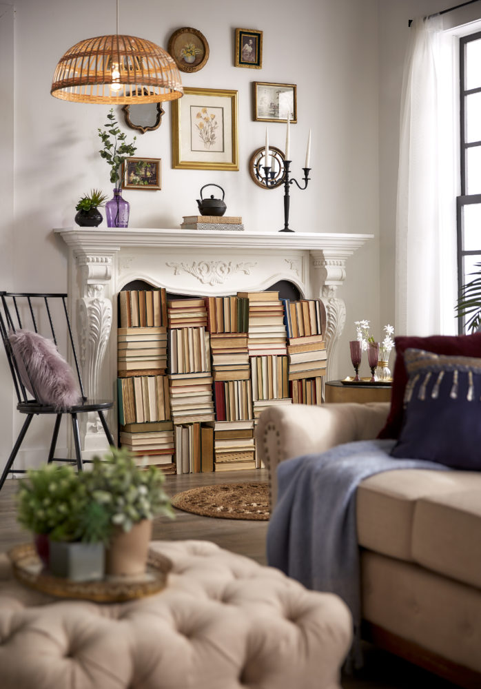Another view of the fireplace filled with books. It also shows the beige linen tufted ottoman and sofa.