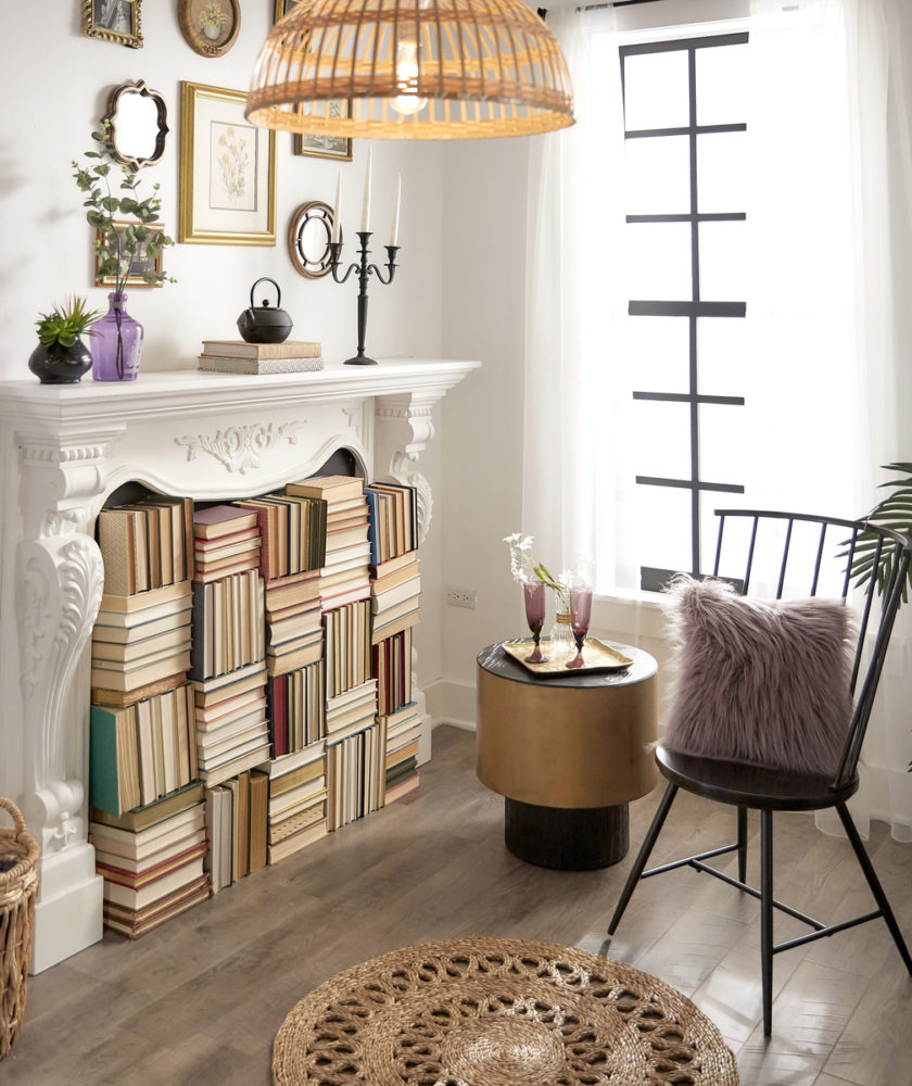 This one corner of the room features a black metal Windsor chair, a shiny gold metal end table, a wicker pendant light, and a fireplace filled with books.