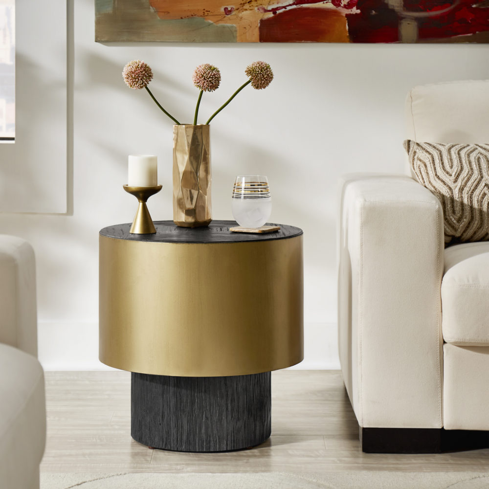 A close-up shot of the round, gold metal and dark brown wood end table.