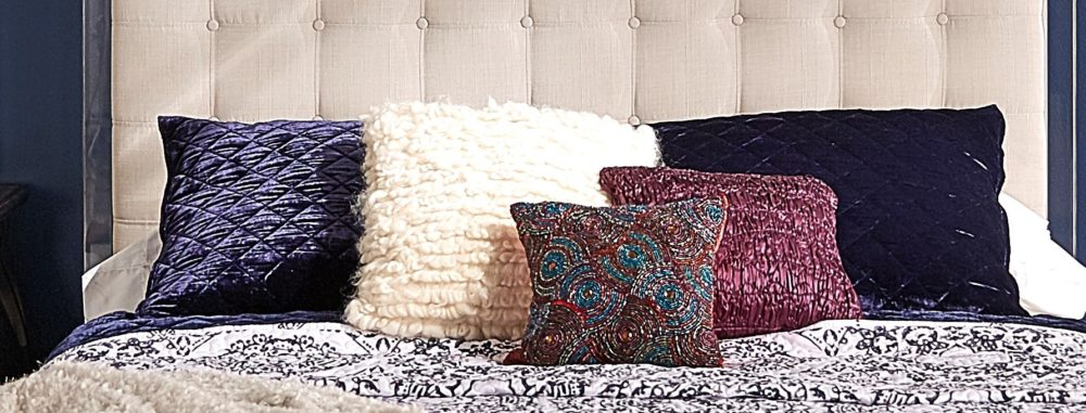 A close-up shot of the bedding. There are many square pillows of all different sizes, colors, and textures.