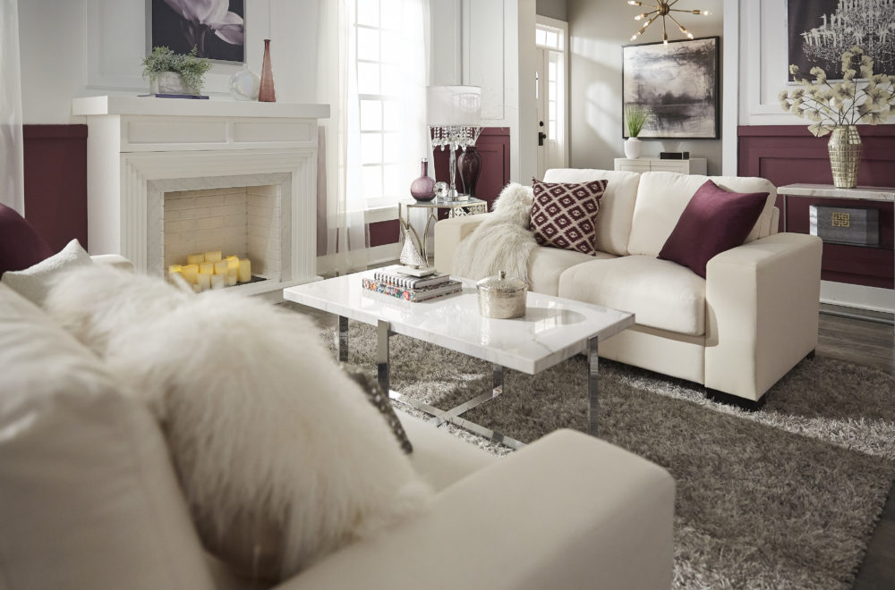 Glam designed living room with side view of white couch, purple pillows and marble cocktail table