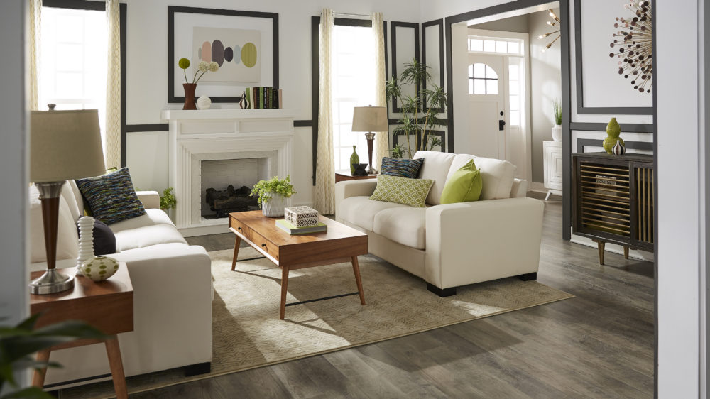 Mid-century designed living room with white couch, green pillows and light wood tables