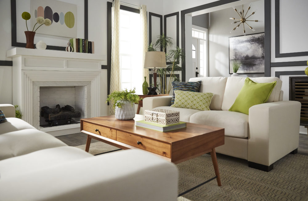 Mid-century designed living room with side view of white couch, green pillows and light wood coffee table