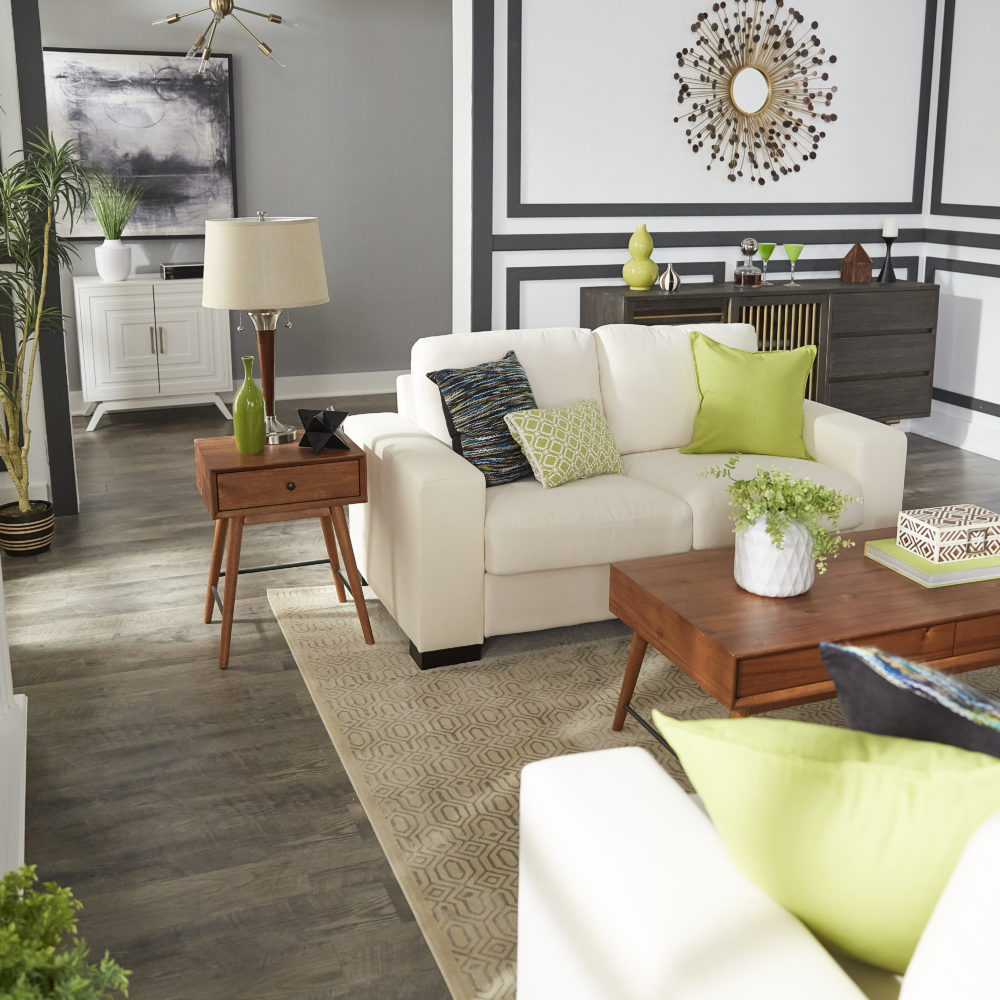 Mid-century designed living room and elevated view of white couch, green pillows and light wood end table