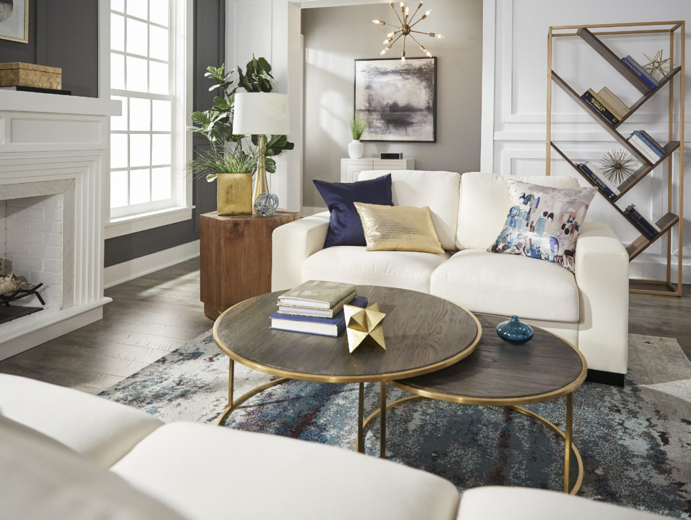 Modern designed living room with front view of white couch, blue and gold pillows, nesting coffee table set and wood end table