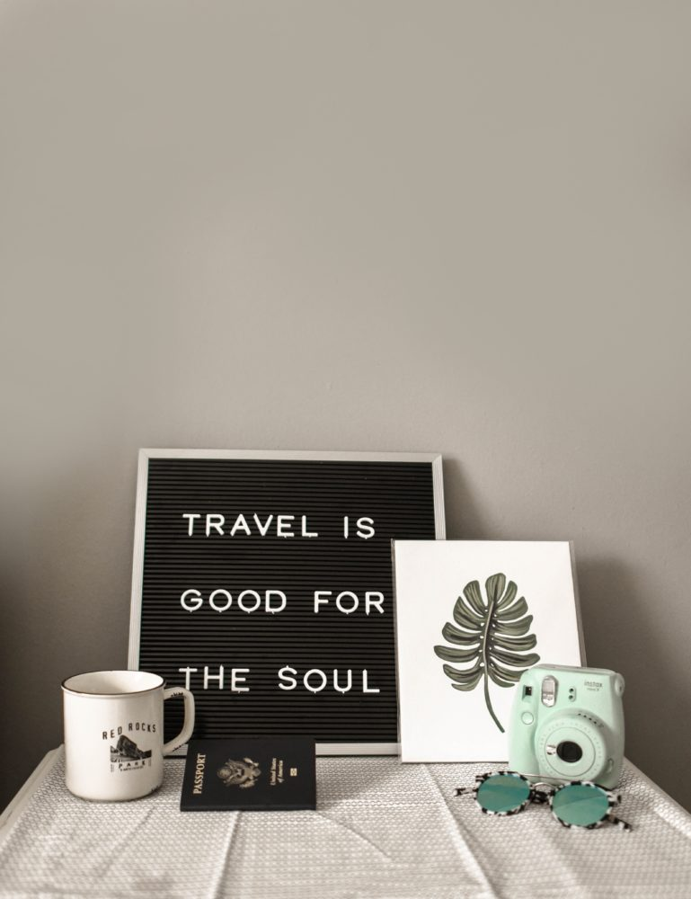 Further reinforcing this one of our tips and tricks for Airbnb posts, we have a travel is good for the soul decorative sign with passport, coffee mug, canvass painting of leaf, Polaroid camera and sunglasses