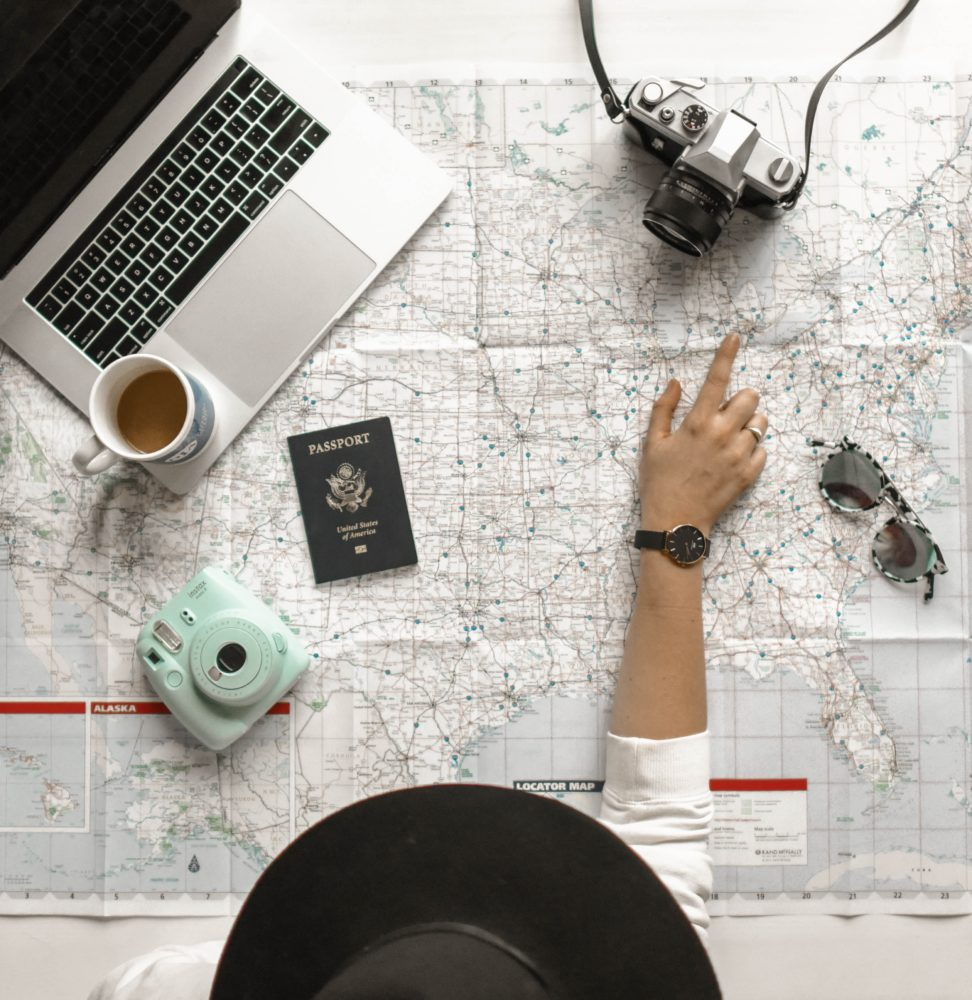 The first of our tips and tricks for Airbnb hosts is all about geography. Here, a woman is pointing at map of U.S. with passport, laptop, coffee mug, Polaroid camera, camera and sunglasses sitting on top.