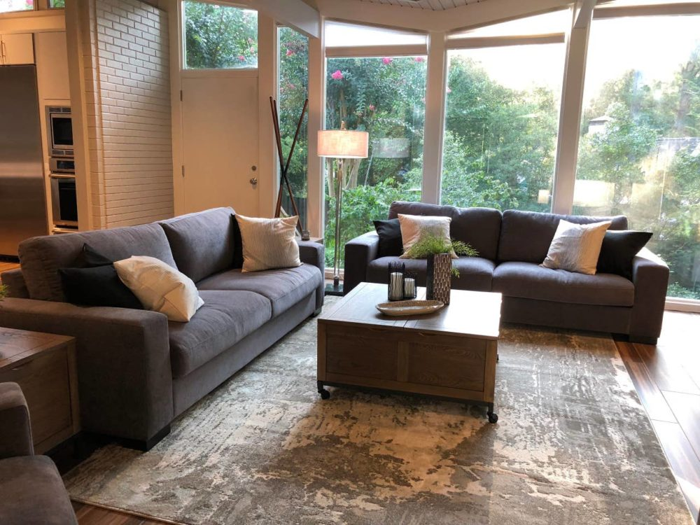 iNSPIRE Q dark grey fabric couches in living room of North Carolina Airbnb.