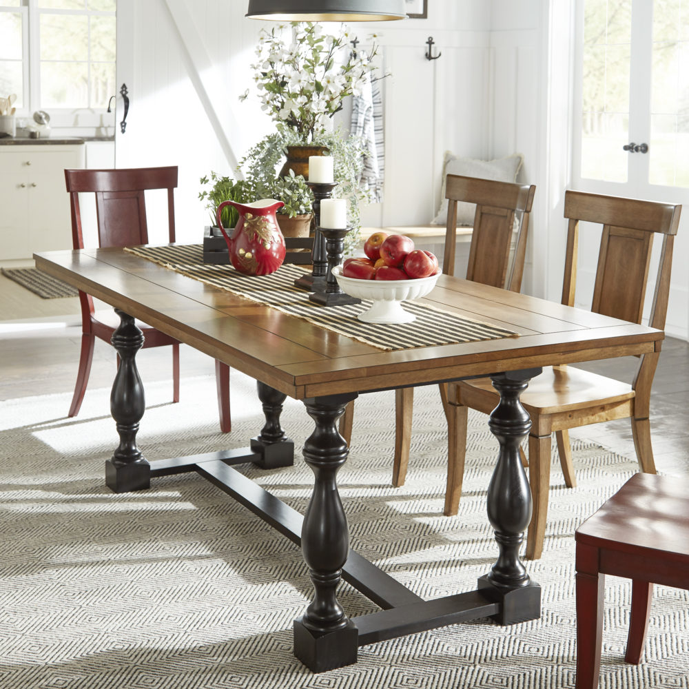 This one of our tips and tricks for Airbnb hosts is all about using large spaces for gatherings. Pictured is the iNSPIRE Q two tone wood dining table with black baluster trestle base and red and oak colored panel back dining chairs.