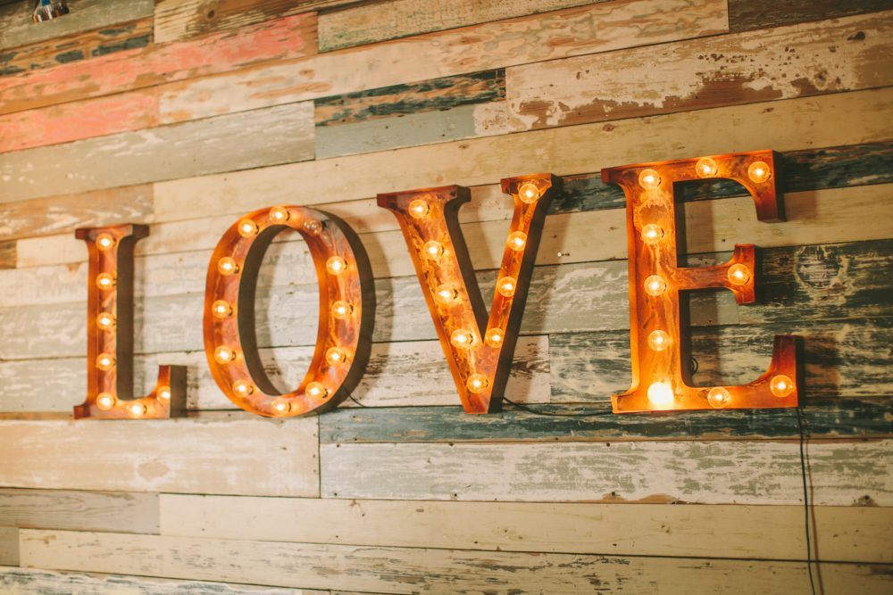 """Since this one of our tips and tricks for Airbnb hosts, pictured here is a rustic metal light up """"Love"""" sign hanging on wall."""