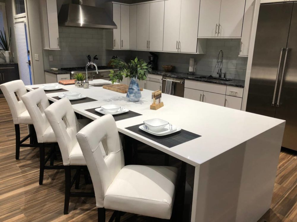 iNSPIRE Q white faux leather upholstered bar stools with key hole back in kitchen of North Carolina Airbnb.